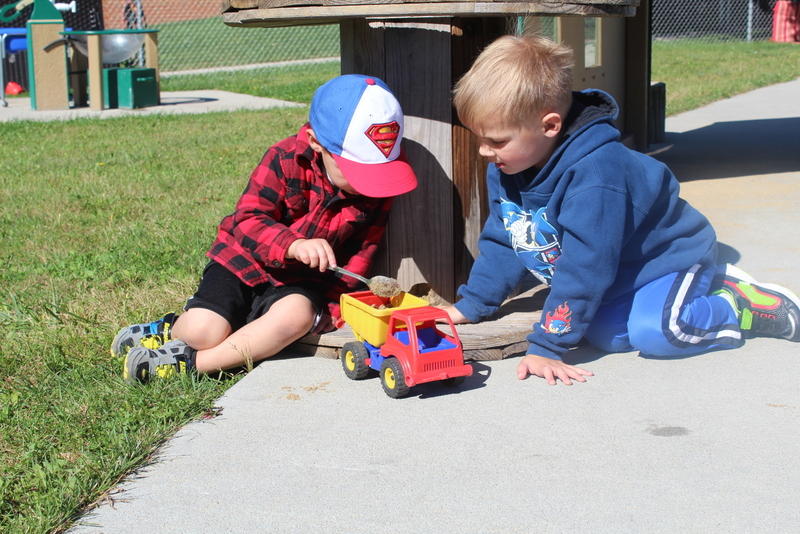 Boys playing with toy truck